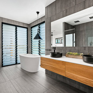 Contemporary master bathroom in Brisbane with a freestanding tub, porcelain tile, porcelain floors, grey floor, flat-panel cabinets, medium wood cabinets, grey walls, a vessel sink and gray tile.