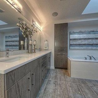 Idee per una grande stanza da bagno padronale design con ante lisce, ante in legno scuro, doccia alcova, WC monopezzo, pareti grigie, lavabo sottopiano, top in quarzo composito, vasca da incasso e pavimento in compensato