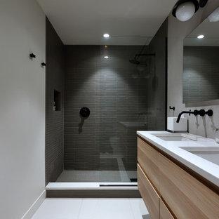 Modelo de cuarto de baño con ducha, minimalista, de tamaño medio, con armarios con paneles lisos, puertas de armario de madera clara, ducha empotrada, sanitario de dos piezas, baldosas y/o azulejos grises, baldosas y/o azulejos de porcelana, paredes grises, suelo de baldosas de porcelana, lavabo bajoencimera, encimera de acrílico, suelo blanco y ducha abierta