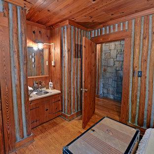 Diseño de cuarto de baño rústico con lavabo encastrado, armarios con paneles lisos y puertas de armario de madera oscura