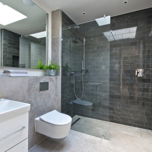 Inspiration for a contemporary shower room bathroom in London with flat-panel cabinets, white cabinets, a corner shower, a wall mounted toilet, black tiles, marble tiles, white walls, a console sink, beige floors and an open shower.