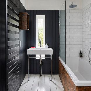 Imagen de cuarto de baño principal, contemporáneo, con bañera encastrada, combinación de ducha y bañera, baldosas y/o azulejos blancos, baldosas y/o azulejos de cemento, paredes negras, suelo de madera pintada, lavabo tipo consola y suelo blanco