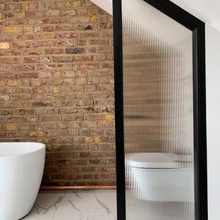 ロンドンの小さいインダストリアルスタイルのおしゃれなマスターバスルーム (置き型浴槽、一体型トイレ、白いタイル、磁器タイル、茶色い壁、磁器タイルの床、白い床、三角天井、レンガ壁) の写真