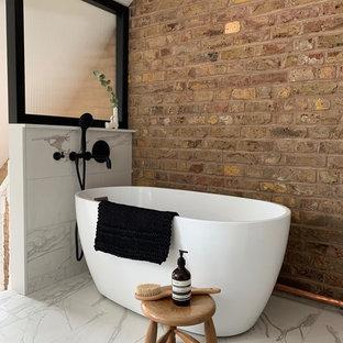 Aménagement d'une petit salle de bain principale industrielle avec une baignoire indépendante, un WC à poser, un carrelage blanc, des carreaux de porcelaine, un mur marron, un sol en carrelage de porcelaine, un sol blanc, un plafond voûté et un mur en parement de brique.
