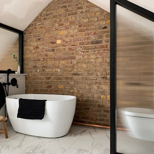This is an example of a small urban ensuite bathroom in London with a freestanding bath, a one-piece toilet, brown walls, white floors, white tiles, porcelain tiles, porcelain flooring, a vaulted ceiling and brick walls.