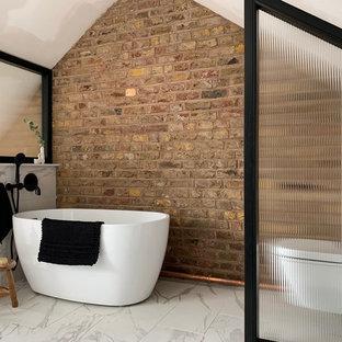 ロンドンの小さいインダストリアルスタイルのおしゃれなマスターバスルーム (置き型浴槽、一体型トイレ、茶色い壁、白い床、白いタイル、磁器タイル、磁器タイルの床、三角天井、レンガ壁) の写真