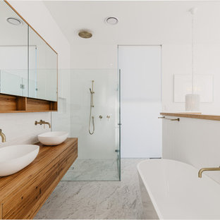 Inspiration for a contemporary bathroom in Sydney with flat-panel cabinets, medium wood cabinets, a freestanding tub, white tile, subway tile, white walls, an undermount sink, wood benchtops, grey floor, brown benchtops, a double vanity and a floating vanity.