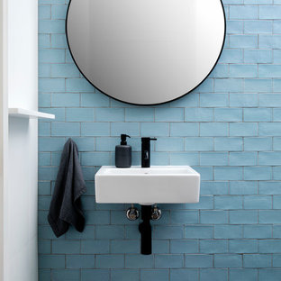 Design ideas for a beach style bathroom in Sydney with blue tile, subway tile, blue walls, a wall-mount sink and grey floor.