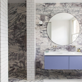 Inspiration for a huge contemporary 3/4 marble tile marble floor and purple floor doorless shower remodel in London with flat-panel cabinets, purple cabinets, multicolored walls, an integrated sink, a wall-mount toilet, solid surface countertops, a hinged shower door and white countertops