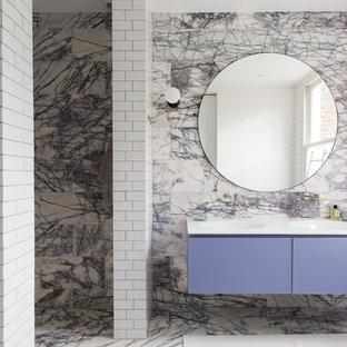 Cette photo montre une très grand salle d'eau tendance avec un placard à porte plane, des portes de placard violettes, un mur multicolore, un lavabo intégré, une douche ouverte, un WC suspendu, du carrelage en marbre, un sol en marbre, un plan de toilette en surface solide, un sol violet, une cabine de douche à porte battante et un plan de toilette blanc.