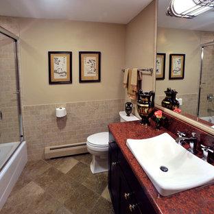 Imagen de cuarto de baño con ducha, tradicional, de tamaño medio, con lavabo encastrado, armarios con paneles empotrados, puertas de armario de madera en tonos medios, encimera de granito, combinación de ducha y bañera, baldosas y/o azulejos beige, baldosas y/o azulejos de cerámica, sanitario de una pieza, paredes beige, suelo de baldosas de porcelana, ducha con puerta corredera y encimeras rojas
