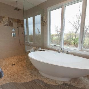 Aménagement d'une grand salle de bain principale contemporaine avec un placard avec porte à panneau surélevé, des portes de placard marrons, une baignoire indépendante, une douche à l'italienne, un WC séparé, un carrelage beige, des carreaux de porcelaine, un mur jaune, un sol en galet, une vasque, un plan de toilette en onyx, un sol gris et aucune cabine.