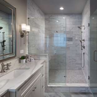 Example of a mid-sized minimalist master gray tile and ceramic tile ceramic tile, gray floor, single-sink and coffered ceiling bathroom design in Atlanta with shaker cabinets, white cabinets, a one-piece toilet, gray walls, an undermount sink, quartz countertops, a hinged shower door, white countertops and a built-in vanity