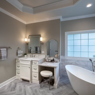 На фото: главная ванная комната среднего размера в стиле модернизм с фасадами в стиле шейкер, белыми фасадами, отдельно стоящей ванной, душем без бортиков, унитазом-моноблоком, серой плиткой, керамической плиткой, серыми стенами, полом из керамической плитки, врезной раковиной, столешницей из искусственного кварца, серым полом, душем с распашными дверями, белой столешницей, унитазом, тумбой под одну раковину, встроенной тумбой и кессонным потолком