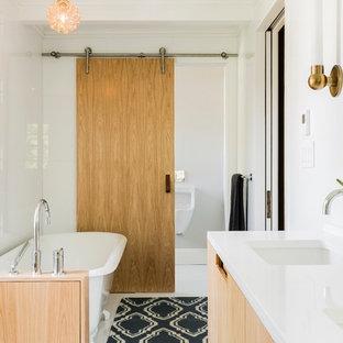 Klassisches Badezimmer mit flächenbündigen Schrankfronten, hellen Holzschränken, Löwenfuß-Badewanne, Urinal, weißer Wandfarbe und Unterbauwaschbecken in Boston