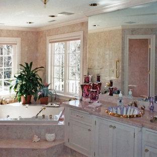 Imagen de cuarto de baño principal, clásico, grande, con armarios con paneles empotrados, puertas de armario marrones, paredes beige, lavabo bajoencimera, encimera de mármol, bañera encastrada, suelo de mármol, suelo rosa, ducha empotrada y ducha con puerta con bisagras
