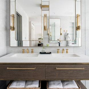 Foto di una grande stanza da bagno minimal con consolle stile comò, ante in legno scuro, piastrelle bianche, pavimento alla veneziana, lavabo integrato, pavimento grigio e top bianco