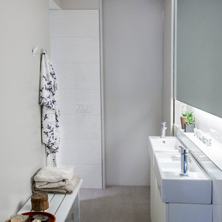 Example of a small minimalist master multicolored tile and porcelain tile porcelain tile and gray floor bathroom design in New York with flat-panel cabinets, white cabinets, a two-piece toilet, white walls, a pedestal sink and tile countertops