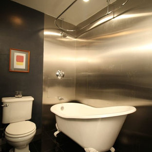 Design ideas for a mid-sized modern master bathroom in New York with a pedestal sink, furniture-like cabinets, dark wood cabinets, solid surface benchtops, a claw-foot tub, a shower/bathtub combo, a two-piece toilet, gray tile, metal tile, beige walls and marble floors.