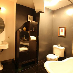 Inspiration for a medium sized retro ensuite bathroom in New York with beige walls, a pedestal sink, freestanding cabinets, dark wood cabinets, solid surface worktops, a claw-foot bath, a shower/bath combination, a two-piece toilet, grey tiles, metal tiles and marble flooring.