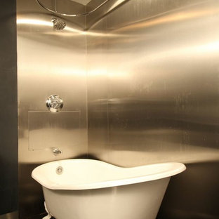 Inspiration for a medium sized retro ensuite bathroom in New York with a pedestal sink, freestanding cabinets, dark wood cabinets, solid surface worktops, a claw-foot bath, a shower/bath combination, a two-piece toilet, grey tiles, metal tiles, beige walls and marble flooring.