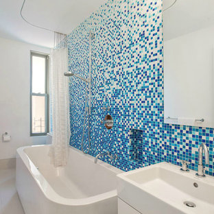 Example of a trendy blue tile and mosaic tile bathroom design in New York with a wall-mount sink and white walls