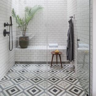 Modelo de cuarto de baño principal, escandinavo, con ducha a ras de suelo, baldosas y/o azulejos de cemento, paredes blancas, suelo de azulejos de cemento, ducha con puerta con bisagras, baldosas y/o azulejos blancos y suelo multicolor