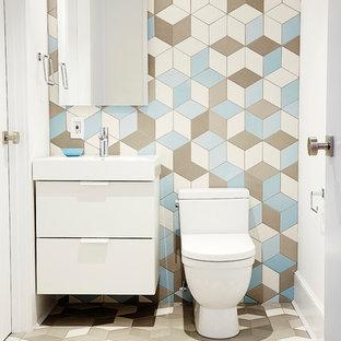 Immagine di una piccola stanza da bagno con doccia design con lavabo sospeso, ante lisce, ante bianche, top in superficie solida, WC monopezzo, piastrelle multicolore, piastrelle in gres porcellanato, pareti multicolore e pavimento in gres porcellanato