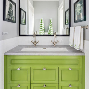 Classic bathroom in New York with recessed-panel cabinets, green cabinets, white tiles, metro tiles, grey walls, a submerged sink, black floors and mosaic tile flooring.