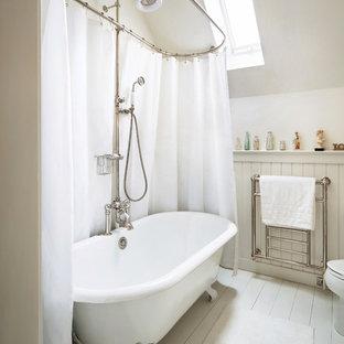 Bild på ett lantligt badrum, med ett badkar med tassar, en dusch/badkar-kombination, vita väggar och målat trägolv