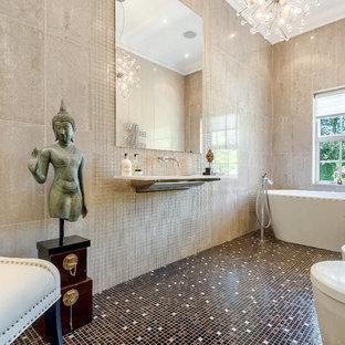 Inspiration for an eclectic ensuite bathroom in Hertfordshire with a freestanding bath, a one-piece toilet, beige tiles, beige walls, mosaic tile flooring, a wall-mounted sink and brown floors.