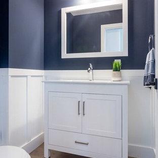 Ejemplo de cuarto de baño con ducha, de estilo americano, pequeño, con armarios estilo shaker, puertas de armario blancas, sanitario de una pieza, paredes azules, suelo laminado, lavabo bajoencimera, encimera de cuarzo compacto, suelo marrón y encimeras blancas