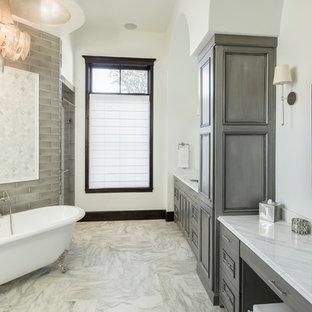 Foto di una grande stanza da bagno padronale vittoriana con ante a filo, ante grigie, vasca con piedi a zampa di leone, piastrelle grigie, piastrelle di vetro, pareti beige, pavimento in marmo, lavabo sottopiano, top in marmo e pavimento bianco