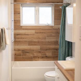 Kleines Modernes Badezimmer En Suite mit flächenbündigen Schrankfronten, weißen Schränken, Badewanne in Nische, Duschbadewanne, Toilette mit Aufsatzspülkasten, braunen Fliesen, Keramikfliesen, weißer Wandfarbe, Mosaik-Bodenfliesen, Laminat-Waschtisch, türkisem Boden und Duschvorhang-Duschabtrennung in Sonstige