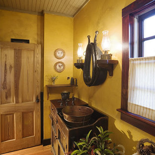 Example of a small mountain style master medium tone wood floor bathroom design in Charlotte with an integrated sink, furniture-like cabinets, dark wood cabinets and copper countertops