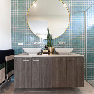 Photo of a contemporary bathroom in Melbourne with brown cabinets, a double shower, blue tile, ceramic tile, white walls, ceramic floors, engineered quartz benchtops, beige floor, a hinged shower door, beige benchtops and a double vanity.