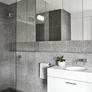 Photo of a mid-sized contemporary 3/4 bathroom in Melbourne with flat-panel cabinets, white cabinets, an open shower, gray tile, porcelain floors, an integrated sink, grey floor, an open shower, white benchtops, a single vanity and a floating vanity.