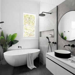 メルボルンの中くらいのコンテンポラリースタイルのおしゃれなマスターバスルーム (フラットパネル扉のキャビネット、白いキャビネット、置き型浴槽、グレーのタイル、白いタイル、ベッセル式洗面器、洗い場付きシャワー、壁掛け式トイレ、セメントタイル、クオーツストーンの洗面台、白い洗面カウンター) の写真