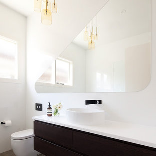 Large trendy master cement tile bathroom photo in Melbourne with a vessel sink, white walls, raised-panel cabinets, dark wood cabinets, a wall-mount toilet, solid surface countertops and white countertops