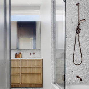 This is an example of a modern bathroom in Melbourne with flat-panel cabinets, light wood cabinets, an alcove tub, a shower/bathtub combo, gray tile, white walls, grey floor, a hinged shower door, white benchtops and a built-in vanity.