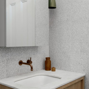 Modern bathroom in Melbourne with flat-panel cabinets, light wood cabinets, gray tile, an undermount sink, white benchtops and a single vanity.