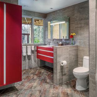 Modern inredning av ett badrum, med keramikplattor, ett nedsänkt handfat, släta luckor, röda skåp och grå kakel