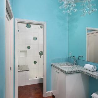 Ejemplo de cuarto de baño actual con lavabo bajoencimera, armarios con paneles lisos, puertas de armario blancas, encimera de vidrio reciclado, baldosas y/o azulejos azules y baldosas y/o azulejos de vidrio