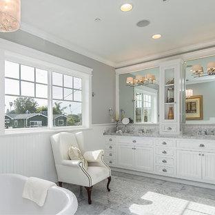 Imagen de cuarto de baño principal, de estilo americano, grande, con lavabo encastrado, puertas de armario grises, encimera de mármol, bañera exenta, baldosas y/o azulejos grises, suelo de mármol y paredes grises