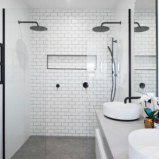 Großes Modernes Badezimmer mit flächenbündigen Schrankfronten, weißen Schränken, weißen Fliesen, Metrofliesen, weißer Wandfarbe, Betonboden, Aufsatzwaschbecken, Beton-Waschbecken/Waschtisch, grauem Boden, offener Dusche, grauer Waschtischplatte und Doppeldusche in Newcastle - Maitland