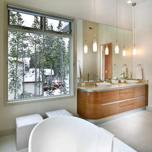 Inspiration for a large contemporary master beige tile and glass tile concrete floor and gray floor bathroom remodel in Atlanta with a vessel sink, flat-panel cabinets, medium tone wood cabinets, granite countertops, white walls and a one-piece toilet
