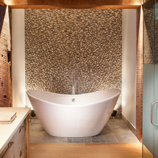 Rustic bathroom in Denver with flat-panel cabinets, medium wood cabinets, a freestanding bath, pebble tiles, white walls, medium hardwood flooring and brown tiles.