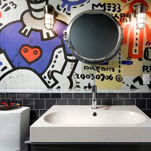 Immagine di una stanza da bagno per bambini american style di medie dimensioni con ante grigie, WC monopezzo, piastrelle nere, pareti multicolore, lavabo rettangolare, ante lisce, vasca ad alcova, vasca/doccia, piastrelle in gres porcellanato e pavimento in gres porcellanato
