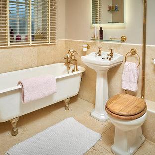 Idee per una stanza da bagno per bambini chic di medie dimensioni con vasca con piedi a zampa di leone, doccia ad angolo, WC a due pezzi, piastrelle in travertino, pareti beige, pavimento in travertino, lavabo a colonna e porta doccia scorrevole