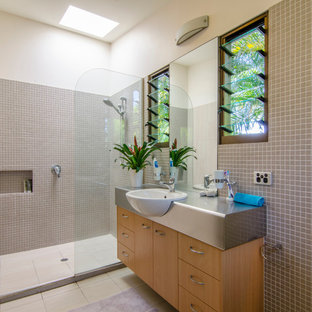 This is an example of a mid-sized tropical master bathroom in Sunshine Coast with a drop-in sink, flat-panel cabinets, light wood cabinets, stainless steel benchtops, an open shower, mosaic tile, white walls, porcelain floors, beige tile and an open shower.